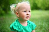 Dziecko siedzi na trawie — Zdjęcie stockowe