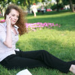 Curly-haired girl with the phone sitting on the grass — Stock Photo