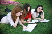 Three girls on the grass ready for lessons — Stock Photo