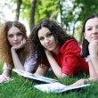 Portrait of three friends studying on the grass — Stock Photo