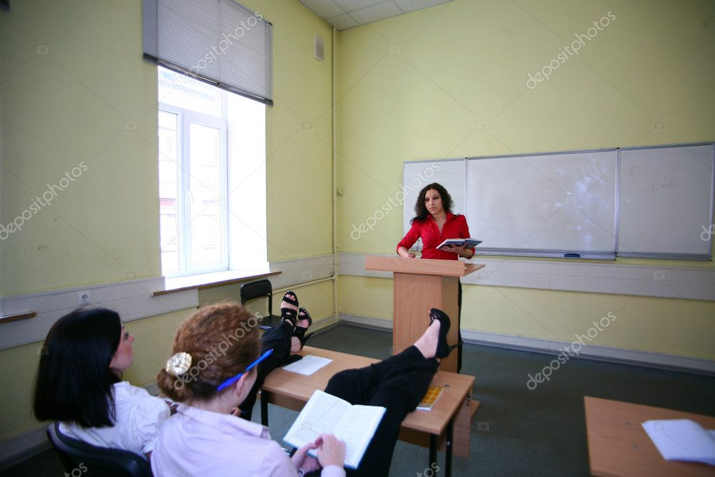 Girl relaxing in the classroom is not paying attention to the teacher — Stock Photo #10640463