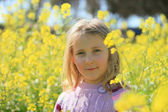 Portrait of a girl on a background of yellow flowers — Stock Photo