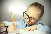 Girl with big glasses learns — Stock Photo