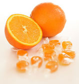 Fresh oranges with candy — Stock Photo