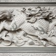 Stone Carving of Qilin on Chinese Temple Wall - Stock Photo