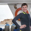 Beautiful scuba diver wears diving suit on boat — Stock Photo