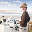 Attractive young woman steering a boat — Stockfoto