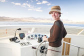 Attractive young woman steering a boat — Stock Photo