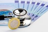 Stethoscope on banknote near euro coin — Stock Photo