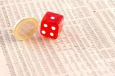 Euro coins and a red dice on the financial newspaper — Stock Photo