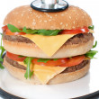 Unhealthy burger with stethoscope — Stock Photo