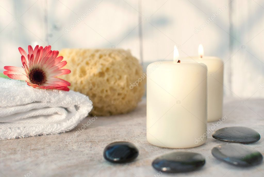 Spa setting with lit candles, zen stones and a natural sponge — Stock Photo #9639878