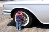 Child Doll Hiding Against Wheel of Antique Car — Stock Photo