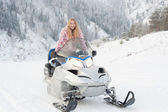 Woman driving a snowmobile — Stockfoto