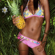 Bikini girl crop with pineapple and tropical plants — Stock Photo