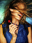 Girl with red lollipop and hair in face — Stockfoto