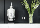 Contemporary interior design detail with buddha image and flower — Stock Photo