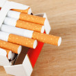 Cigarettes in pack on the breadboard — Stock Photo