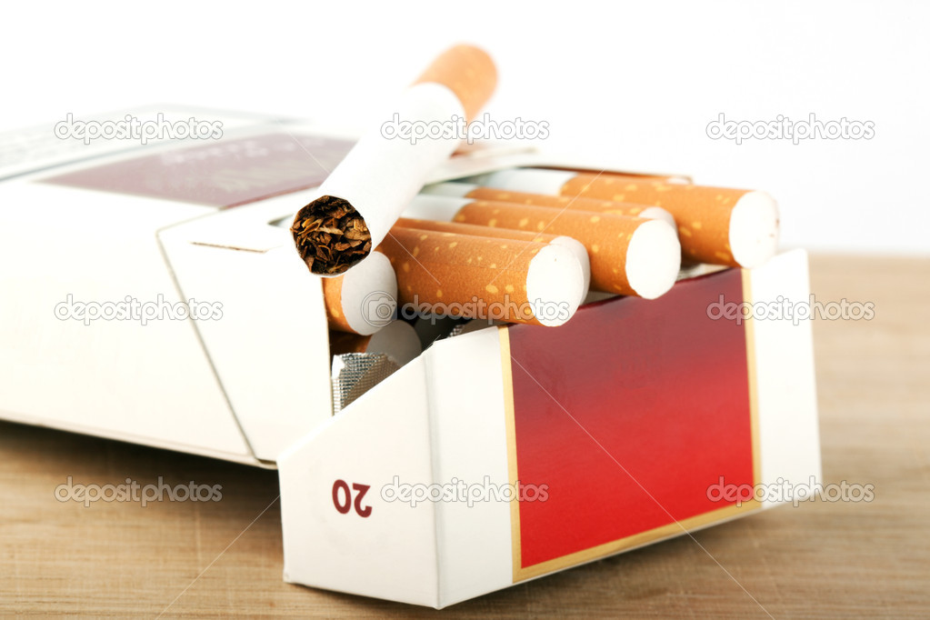 Several Cigarettes in pack on the breadboard — Stock Photo #8385891