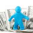 Plasticine man with banknote - Stock Photo