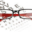 Reading glasses with eye chart - Stock Photo