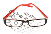 Reading glasses with eye chart — Stock Photo