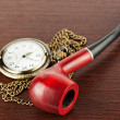 Pocket watch and smoking tube — Stock Photo