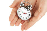 Alarm clock with hands — Stock Photo