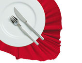 Fork, knife and white plate on a red cloth isolated on white — Stock Photo