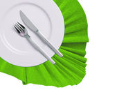 Fork, knife and white plate on green cloth isolated on white — Stock Photo