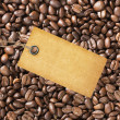 Paper tag over coffee beans background — Stock Photo