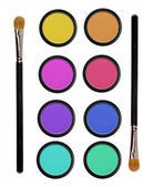 Colorful eyeshadows in black boxes and two brushes isolated on w — Stock Photo