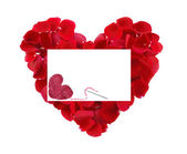 Beautiful heart of red rose petals and greeting card with textil — Stock Photo