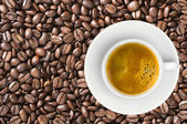 White cup of coffee espresso over coffee beans background — ストック写真