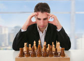 Serious man thinks on game of chess — Stock Photo
