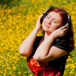 Redhead pretty girl with headphones listening to music in nature — Stock Photo