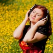Stock Photo: Redhead pretty girl with headphones listening to music in nature