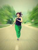 Happy, cheerful girl running down the road — Stock Photo
