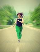 Happy, cheerful girl running down the road — Stock Photo