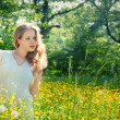 Beautiful young girl in nature, in a field of flowers — Stock Photo #10665636