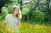 Beautiful young girl in nature, in a field of flowers — Stock Photo