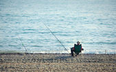 Fisherman with a fishing rod fishing on the background of sea — Stock Photo