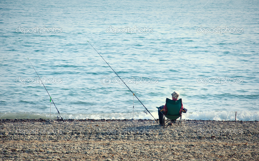 Fisherman with a fishing rod fishing on the background of the sea — Stock Photo #10665777