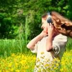 Beautiful girl in headphones enjoying the music with flowing hai — Stock Photo #10718834