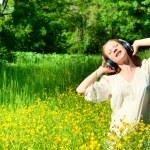 Beautiful girl in headphones enjoying the music in a field of fl — Stock Photo #10718979