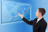 Businessman and a modern blue map with charts and graphs — Stock Photo