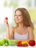 Beautiful girl with vegetables in the kitchen — Stock Photo