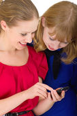 Two happy pretty girls with a mobile phone — Stock Photo