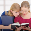 Two cute girls college reading book - Stock Photo
