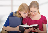 Two cute girls college reading book — Стоковое фото
